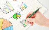 Obchodní osoba pobírající barevné grafy a ikon na papíře — Stock fotografie