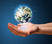 Woman holding a glowing earth globe — Stock Photo