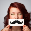 Happy cute girl holding paper with mustache drawing  — Stock Photo #46635827