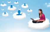 Young woman sitting in cloud with laptop — Stock Photo