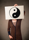 Woman holding a paper with a yin-yang on it in front of her head — Stock Photo