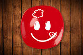 Happy smiley cartoon face on colorful dish plate — Stock Photo