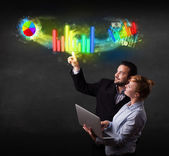 Young business couple touching colorful modern graph system conc — Stock Photo