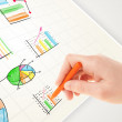 Business person drawing colorful graphs and icons on paper — Stock Photo #47407187
