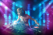Dziewczyna dj miksowania muzyki w klubie z niebieski i fioletowy światła — Zdjęcie stockowe