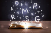 Open book with glowing letters flying out — Stock Photo