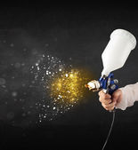 Worker with airbrush painting with glowing golden paint  — Stock Photo