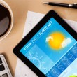 Tablet pc showing weather forecast on screen with a cup of coffe — Stock Photo #47863067