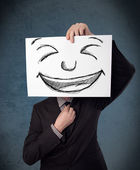 Empresario sosteniendo un papel con cara sonriente frente a su hea — Foto de Stock