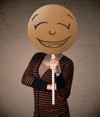 Joven sosteniendo una junta cara sonriente — Foto de Stock
