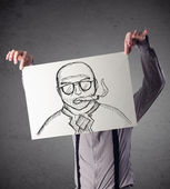 Businessman holding a cardboard with a smoking man on it in fron — Stock Photo
