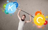 Skinny guy lifting colorful vitamin weights — Stock Photo