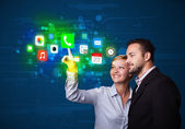 Young business couple pressing colorful mobile app icons with bo — Stock Photo