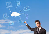 Handsome man looking at cloud computing concept on blue sky — Stock Photo