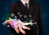 Young businessman presenting colorful glowing social media icons — Stock Photo