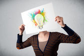 Woman holding a cardboard with paint splashes and lightbulb in f — Stock Photo