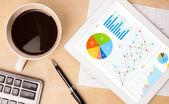 Tablet pc toont grafieken op scherm met een kopje koffie op een bureau — Stockfoto