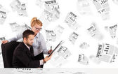 Business man and woman at desk with stock market newspapers — Stock Photo