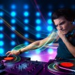 Young Dj mixing records with colorful lights — Stock Photo #48512919