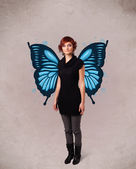 Young girl with butterfly blue illustration on the back — Stock Photo