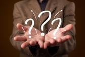 Young businessman presenting hand drawn question marks — Stock Photo