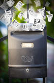 Post box with daily newspapers flying — Stok fotoğraf