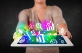 Young person holding tablet with graph and chart symbols — Stockfoto