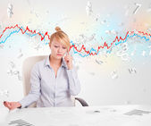 Business woman sitting at table with stock market graph  — Zdjęcie stockowe