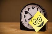 Nota post-it con cara sonriente sticked en reloj — Foto de Stock