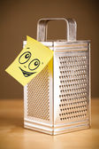 Post-it note with smiley face sticked on grater — Stock Photo