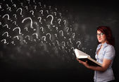 Pretty woman reading a book with question marks coming out from  — Stock Photo