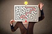 Frau hält ein papier mit einem labyrinth darauf vor ihre hea — Stockfoto