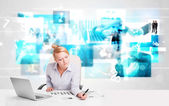 Business person at desk with modern tech images at background — Stock fotografie