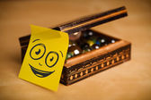 Post-it note with smiley face sticked on jewelry box — Stock Photo