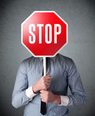 Businessman holding a stop sign — Stock Photo