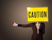 Bir uyarı işareti tutan genç kadın — Stok fotoğraf
