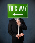 Businessman holding a direction sign — Stock Photo