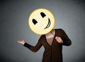 Young woman holding a smiley face emoticon — Stock Photo