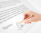 Hand writing personal signature on a paper form — Stock Photo