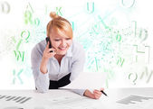 Business woman at desk with green word cloud — Stock Photo