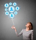 Woman holding social network balloon — Stock Photo