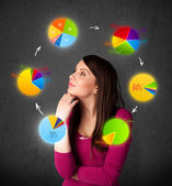 Young woman thinking with pie charts circulation around her head — Stock Photo
