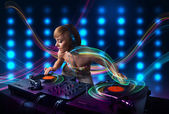 Young Dj girl mixing records with colorful lights — Stockfoto