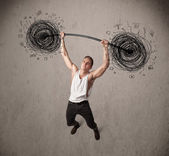 Muscular man lifting chaos concept — Stock Photo