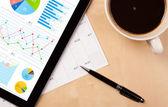Tablet pc muestra gráficos en pantalla con una taza de café en un escritorio — Foto de Stock