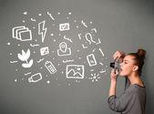 Photographer girl capturing white photography icons and symbols — Stock Photo