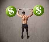 Muscular man lifting green dollar sign weights — Stock Photo