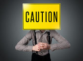 Businessman holding a caution sign — Stock Photo