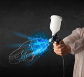 Worker with airbrush gun painting hand drawn car lines — Stock Photo