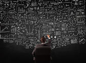 Businessman sitting in front of a blackboard with charts — Stok fotoğraf